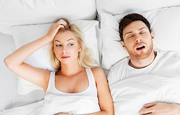 unhappy woman lying in bed with snoring man
