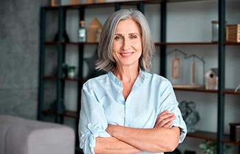 Smiling confident stylish mature middle aged woman standing at home office