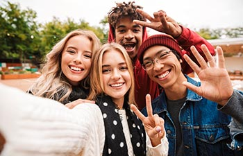 Group if cheerful multiethnic friends teenagers spending fun time together outdoors, taking a selfie