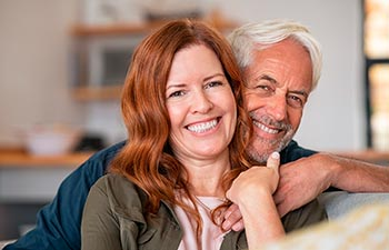 Portrait of middle aged couple hugging and looking at camera