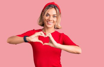 Smiling woman showing heart shape with her hands.