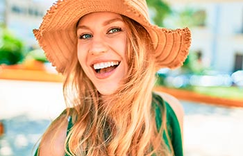 Young beautiful blonde woman on vacation wearing summer hat