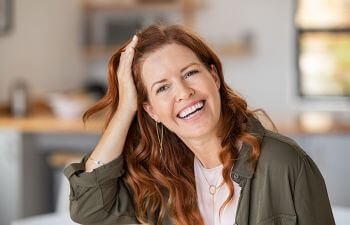 Smiling middle-aged woman combing her hair with her right hair.