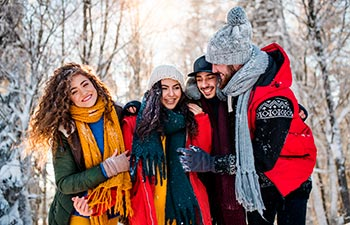 A group of young friends on a walk outdoors in snow in winter forest