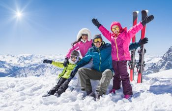 Family of four having fun while skiing in the mountains.