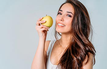 a young woman holding an apple